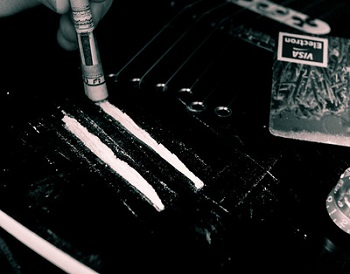 Rows of cocaine on a table with a rolled-up bill to sniff them with.