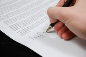 A hand signing a name on the signature line of a legal document.