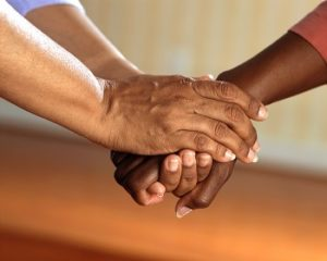 Two arms interlock and hold hands