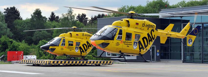 """Ulmer Rettungshubschrauber auf dem Weg nach Neuseeland Der Ulmer Rettungshubschrauber, bekannt unter seinem Funkrufnamen """"Christoph 22"""", wurde am Pfingstsamstag gegen einen anderen Hubschrauber getauscht. Die bisherige Maschine vom Typ BK-117 B2 wurde vom Betreiber ADAC nach Neuseeland verkauft. Als Ersatz kam eine nahezu typgleiche Maschine wieder nach Ulm.  Seit der ADAC im Jahr 2003 von der Bundeswehr den Flugbetrieb des Ulmer Rettungshubschraubers übernahm, war die 1985 gebaute Maschine mit der Luftfahrtkennung D-HBND der Ulmer Stations-Hubschrauber. Nur, wenn Wartungen oder Reparaturen notwendig waren, war eine Ersatzmaschine im Einsatz.  Schrittweise modernisiert die ADAC Luftrettung ihren rund 50 Hubschrauber starken Gerätepark auf den seit diesem Jahr eingesetzten Typ H 145 T2. Vom bisherigen Hubschrauber-Typ konnte 14 Stück an einen neuseeländischen Luftretter verkauft werden. Nachdem nun die Ulmer Maschine aufgrund ihrer Flugstunden zu einer größeren Wartung in die Werft nach Landshut musste, wurde vom ADAC entschieden, dass die Maschine gleich für Neuseeland verkaufsfertig gemacht wird.  Die für Ulm eingeplante neue Maschine H 145 T2 wird nach den Worten von ADAC-Sprecher Jürgen Griewing vermutlich im Jahr 2017 geliefert werden. Um die jährlich über 1.500 Ulmer Luftrettungseinsätze abwickeln zu können war daher eine Zwischenlösung notwendig.  Am Samstagnachmittag traf daher die D-HSMA aus Landshut ein, um zukünftig der Ulmer Stamm-Hubschrauber zu sein. Wie eine Flucht wirkte es dabei, dass zeitgleich die D-HBND zu einem Einsatz alarmiert wurde. Der alte Hubschrauber brach zu einem Notfall auf, während der neue Hubschrauber bereits über dem Landeplatz am Ulmer Eselsberg einschwebte.  Während sich die diensthabende Notärztin auf dem bisherigen Hubschrauber um eine Patientin kümmerte, wurde bereits der neue Hubschrauber in den Hangar gebracht und sofort mit den zusätzlichen Ulmer Beschriftungen versehen. Die Schriftzüge """"Bundeswehrkrankenhaus Ulm"""" auf den Tü"""
