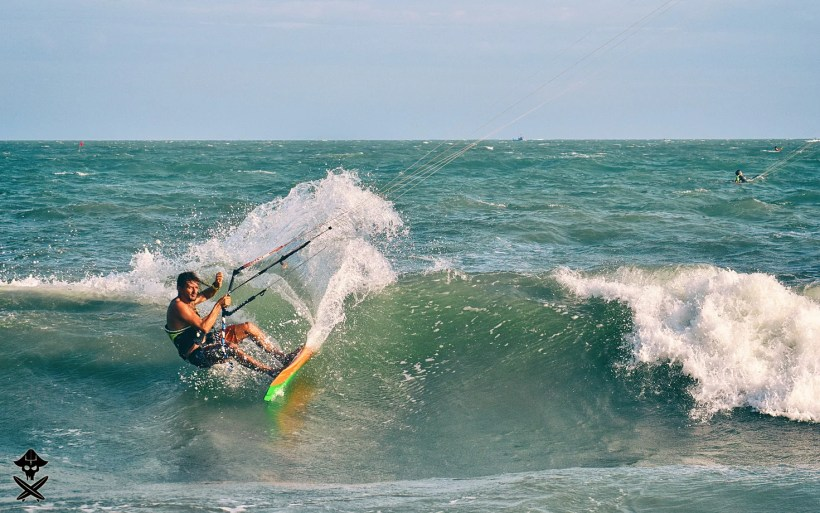 riding the shore break wave in Mui Ne on a surfboard and kite