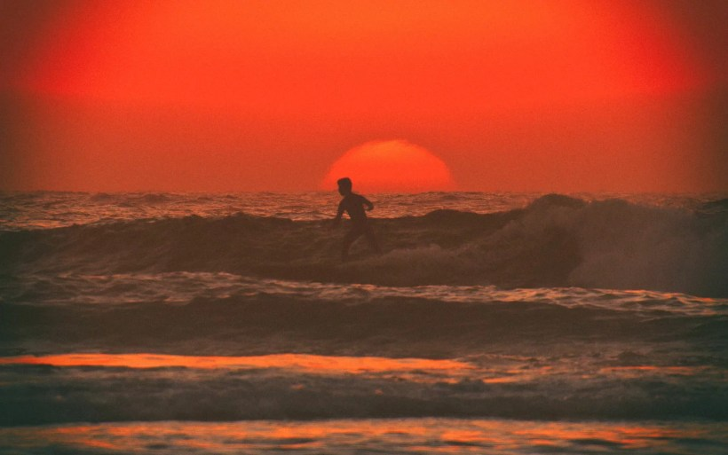 surfer in maroc surf the wave at the sunset just silhouette is visible
