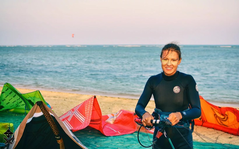 smiling kite girl is winding lines on a bar after kitesurfing session in Phan Rang