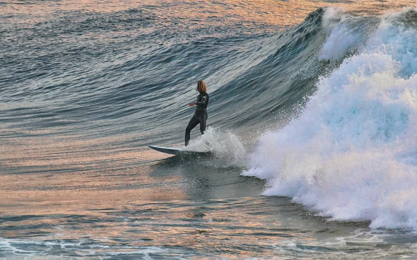 surfer on a short board is making bottom turn on a big wave in morocco imsouane cathedral