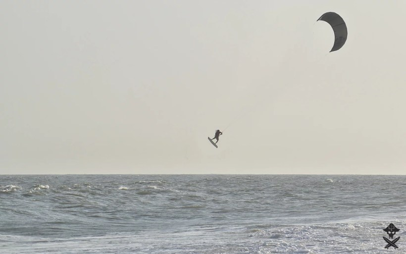 silhouette of a kitesurfer with black kite doing kite loop during competition in Mui Ne Vietnam 2018