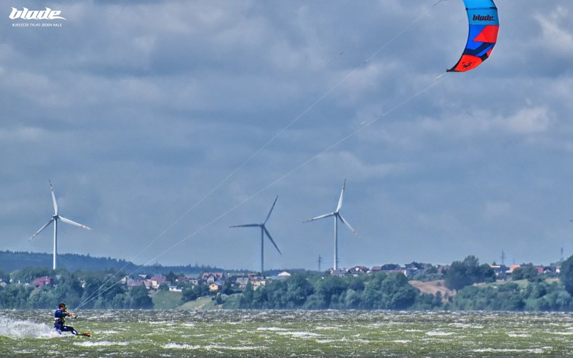 Artur Sowa is riding on the Puck gulf in hel peninsula with blade kite and wind mills in the bakcground