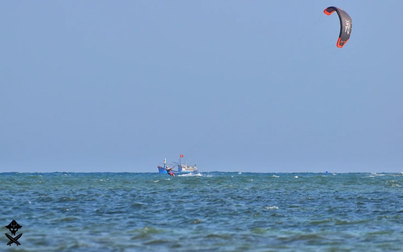 long distance shot showing kitesurfers riding far from the shore with the fishermen boat behind him in Phan Rang lagoon best kitesurfing spot in Vietnam