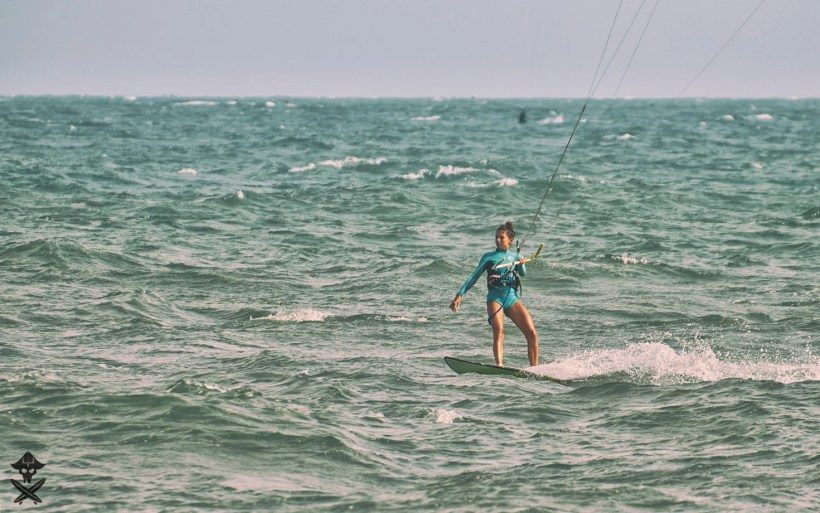 german kite girl instructor very fit and neat riding on a kite surf board in clingy wetsuit at mui ne vietnam 2018