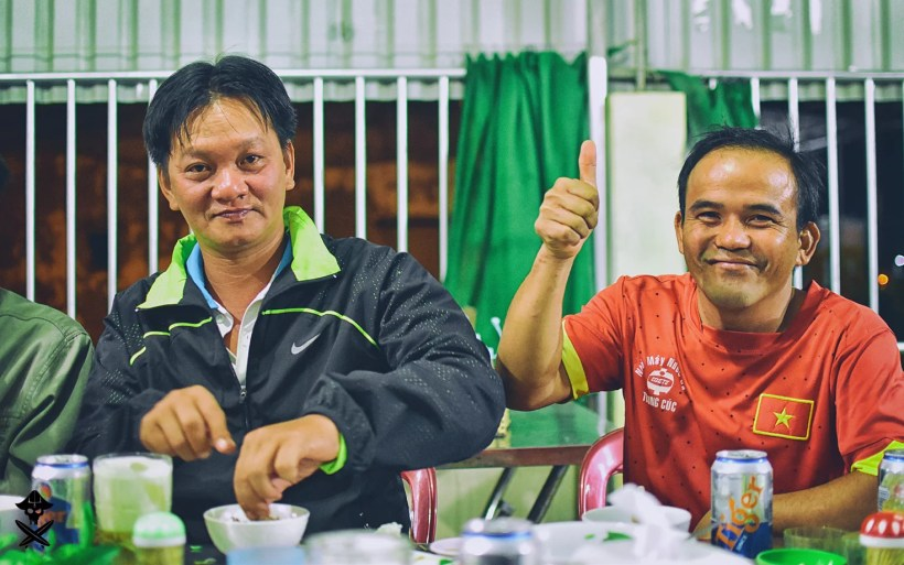 portrait of two vietnamese teachers eating and drinking tiger bear in Phan Rang