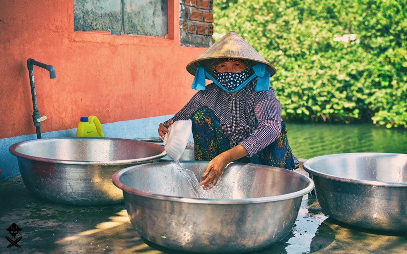 portrait of a sitting vietnamese women in mask and traditional hat washing the dishes