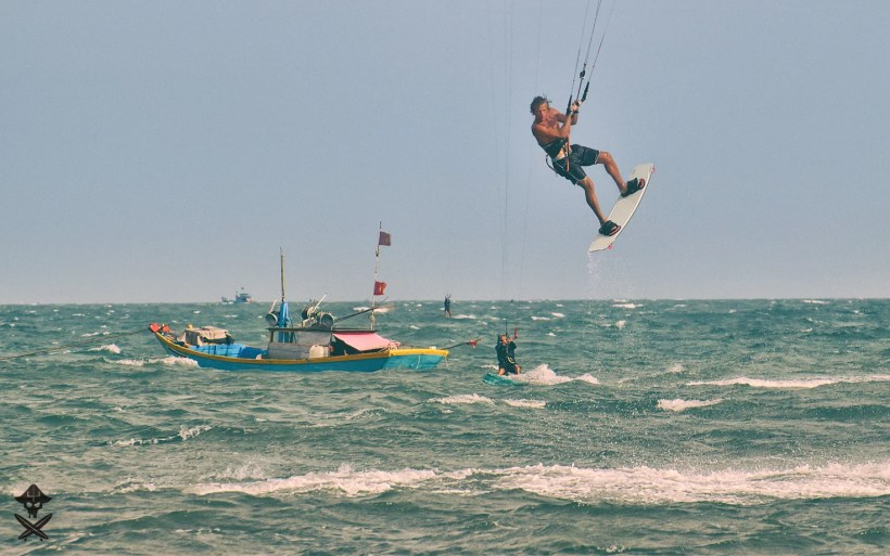Peter Kiss owner at surfpoint jumpin on a kite with the fishermen boat in the background in mui ne beach vietnam 2018
