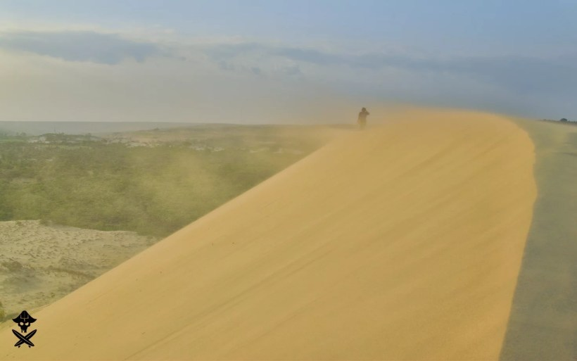man standing on top of dune close to mui ne vietnam the wind is blowing very hard