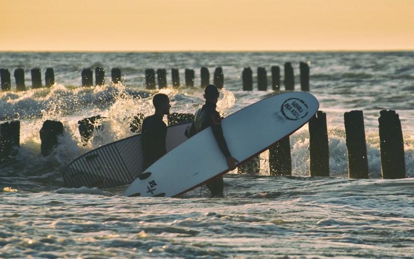 surferzy z deskami idą po plaży w chałupach przy zachodzącym słońcu