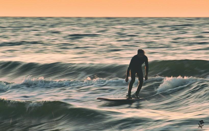 surfing przy zachodzącym słońcu w chałupach na bałtyku