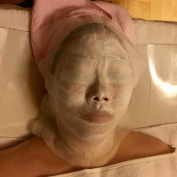 A super thick modeling mask is painted on top of the first mask, during a facial in Seoul.