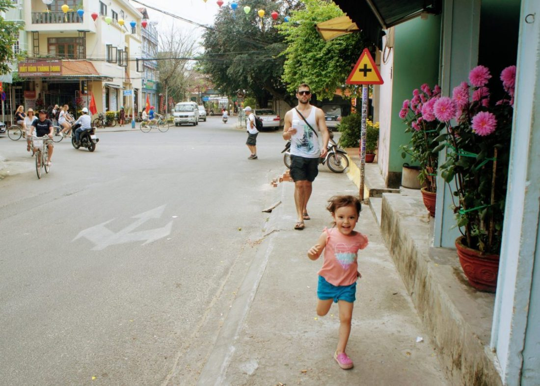child running on the streets of hoi an vietnam