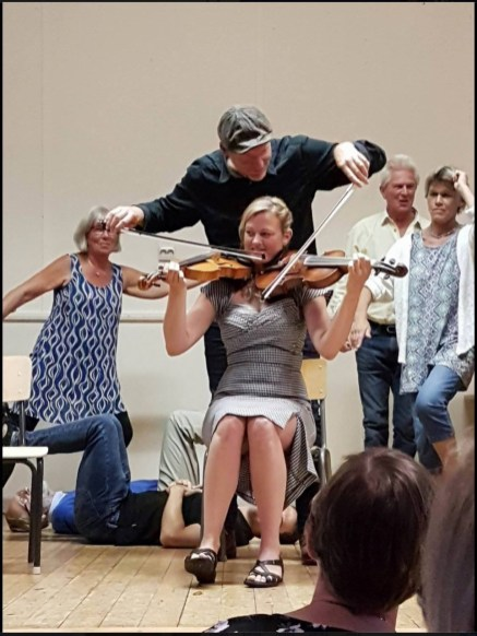 the ensemble class also made a nice song for our teachers, to lull them into a false sense of security before challenging them to a stunt. we demonstrate our various new exercises behind them on stage. thanks to a FB friend of Mia's for the photo.