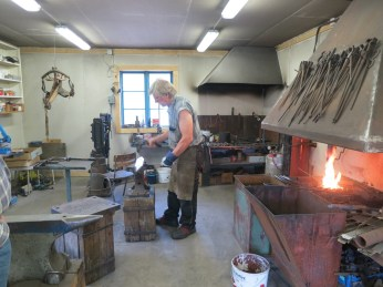 the blacksmith at work making a set of hooks
