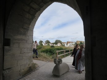 the city wall has lots of arches, each populated by a ram