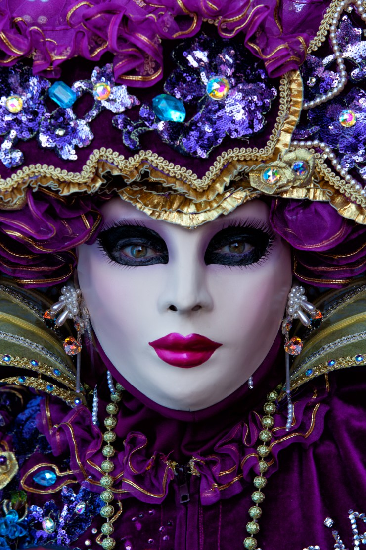 Close-up portrait of a gorgeous Carnival model in a bright purple costume