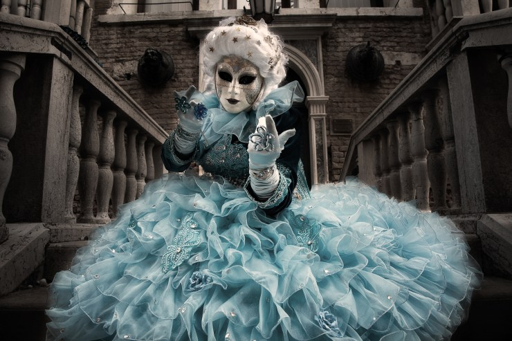 Blue costumed Carnival model calling from a stairway in Venice