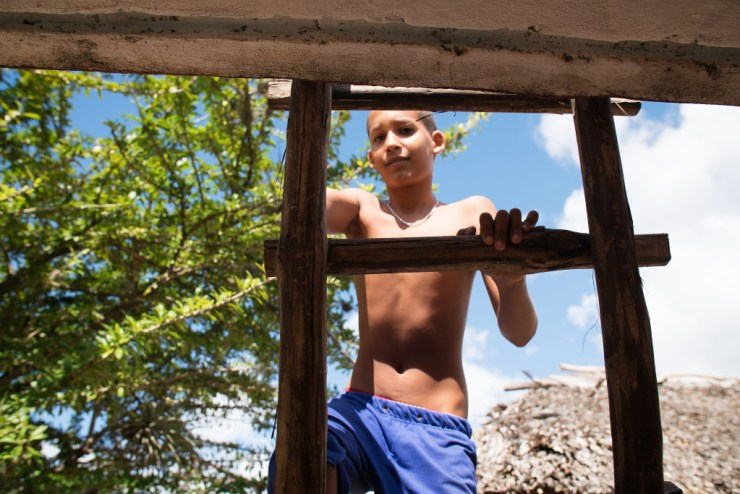 A young boy climbs the ladder to the roof of his family home on the road to Baracoa in Eastern Cuba. Photographed on a Tamron 24-70 f/28 at 1/640 at f/3.2.
