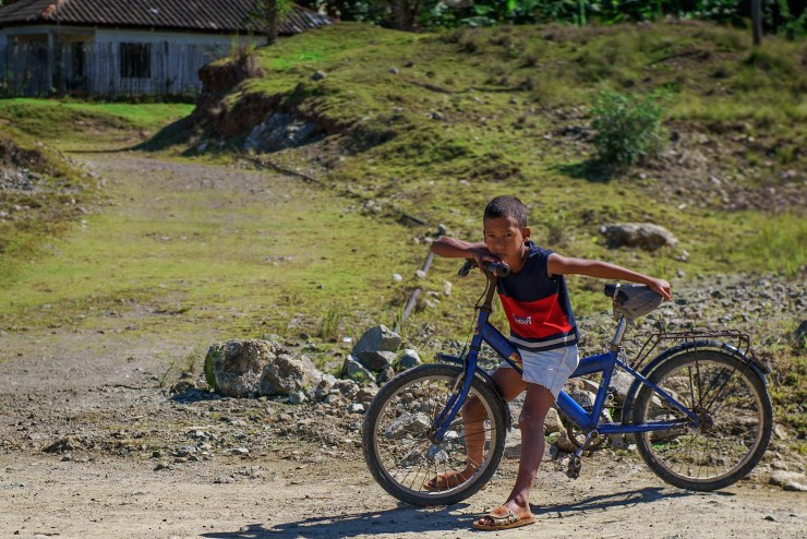 A boy rests on his bike on the road between Baracoa and Moa. Photographed with a Tamron 24-70mm f/2.8 at 1/6400 and f/2.8.