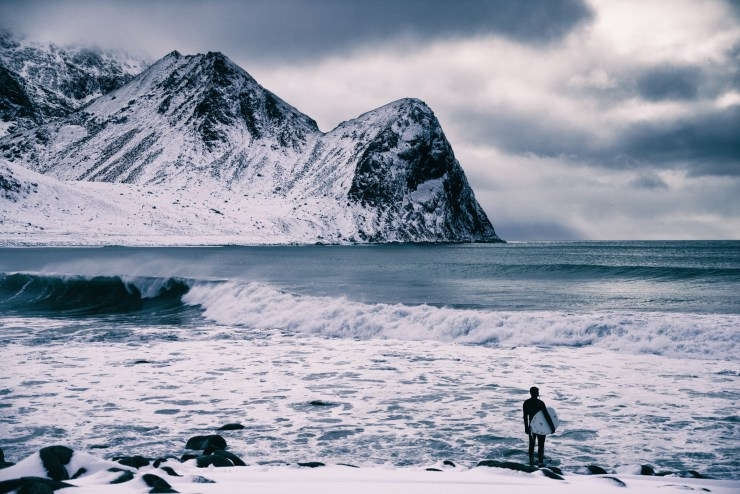 A surfer looks over the icy waters before jumping in for a session in Arctic Norway. Photo by Michael Bonocore.
