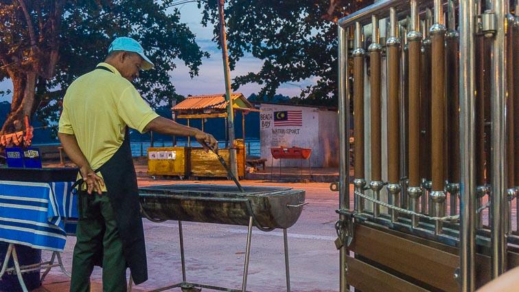 Man making freshly made satay on the streets of Pangkor