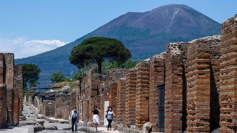 Visitors walk across the archeological site of Pompeii at the bottom of the Mount Vesuvius volcano (Rear) on May 26, 2020, as the country eases its lockdown aimed at curbing the spread of the COVID-19 infection, caused by the novel coronavirus. - Italy's world-famous archeological site Pompeii reopened to the public on May 26,bBut with foreign tourists still prohibited from travel to Italy until June, the site that attracted just under 4 million visitors in 2019 is hoping that for now, Italian tourists can make up at least a fraction of the difference. (Photo by Tiziana FABI / AFP) (Photo by TIZIANA FABI/AFP via Getty Images)