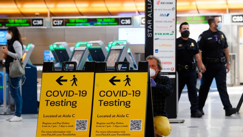 A traveler takes a photo of a Covid-19 testing sign at  Los Angeles International Airport (LAX) in February 2021.