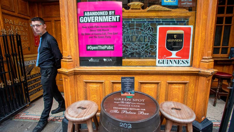 An employee wearing a face visor due to the COVID-19 pandemic, waits to serve customers outside a pub in Dublin on September 18, 2020, following reports that further lockdown restrictions could be imposed to help mitigate the spread of the novel coronavirus. - Ireland's capital could face further restrictions this weekend after public health experts raised concerns when its 14-day incidence rate jumped to more than 100. (Photo by Paul Faith / AFP) (Photo by PAUL FAITH/AFP via Getty Images)