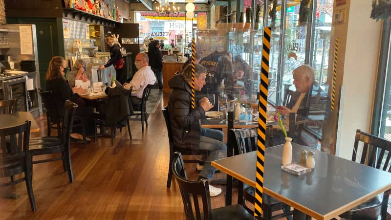 Above, people eat indoors as indoor dining continues to open up in New York City on March 24. Physical distancing, barriers and good ventilation are a few ways to reduce Covid-19 risk.