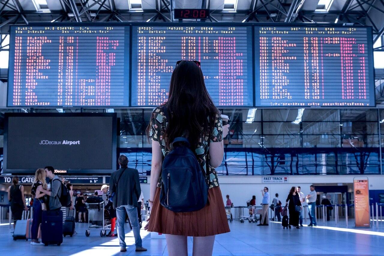 空港で電光掲示板を見る女性