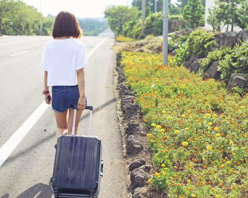 スーツケースを持って歩く女性