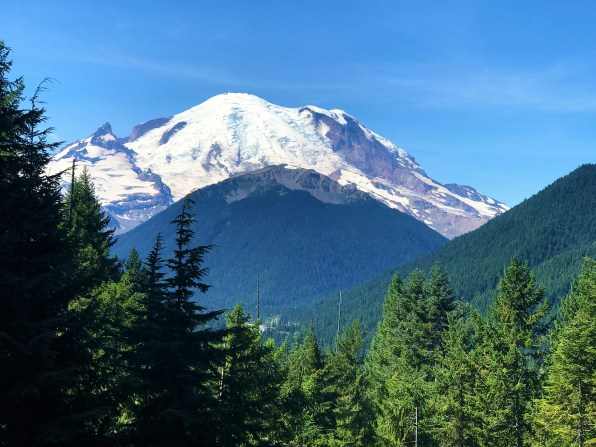 View of Mount Rainier along with green ranges of mountains in Mount Rainier National Park.  Easy Hikes and Road side attractions at Mount Rainier.