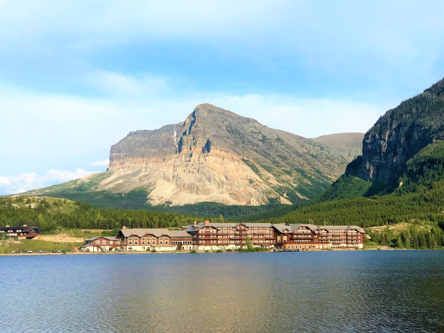 Stunning view of huge mountains and Many Glacier Hotel from Swiftcurrent Lake Nature trail