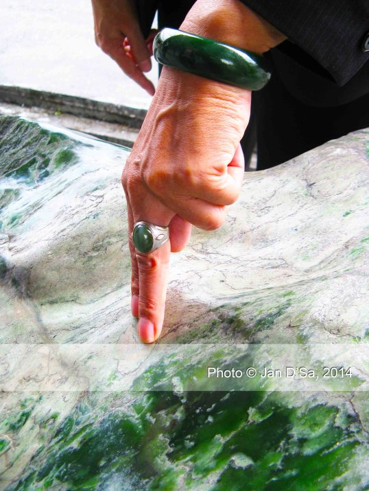 This lady is wearing a green jade bangle, a green jade ring and gestures to a huge green jade boulder.