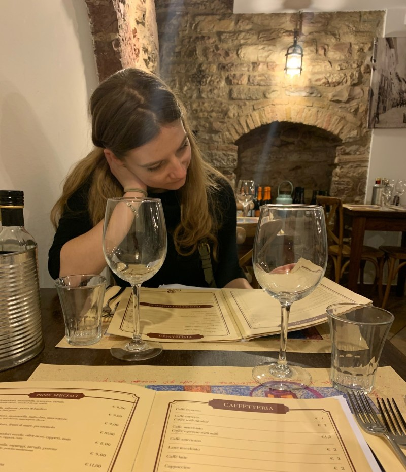 A person sitting at a table with wine glasses  Description automatically generated