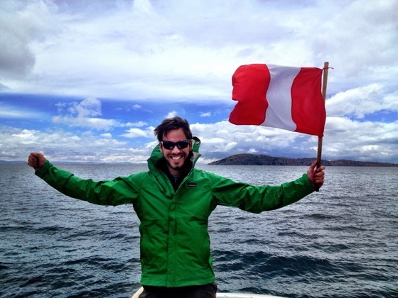Simon Heyes of Simons Jam Jar with the flag of Peru at Lake Titicaca