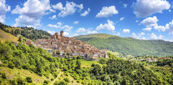 Beautiful view of idyllic village Castel del Monte, set into a steep hillside under apennine mountain peaks on a sunny summer day, Gran Sasso e Monti della Laga National Park, L'Aquila, Abruzzo, Italy