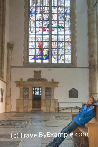 Roman is looking at one of the windows of Sint-Janskerk and listening to the audio guide
