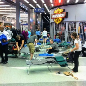 People Camping Out on Airport Cots