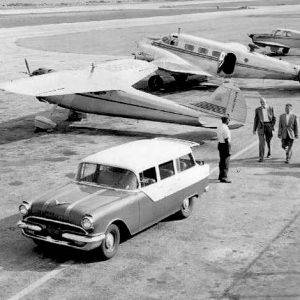 Old cars and planes on a runway