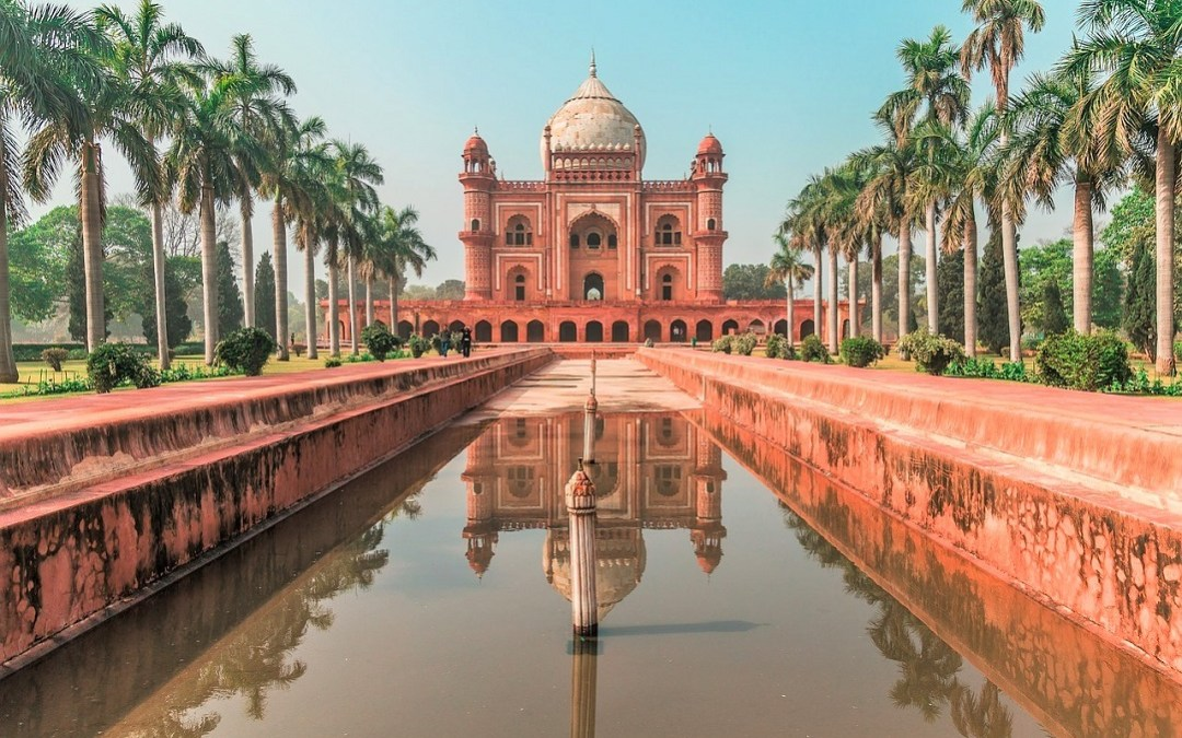 A central waterway, lined with palm trees leads to a view of the terracotta-coloured Humayun Temple in Delhi, India