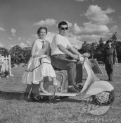 A young couple in typical 50s style sit on a scooter in a vehicle parade at the Royal Show. Kenya, 25 September 1957