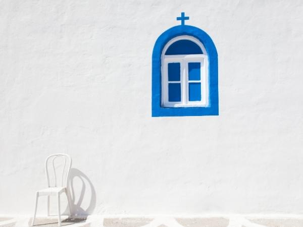 Una finestra blu sul muro bianco di una chiesa in Grecia