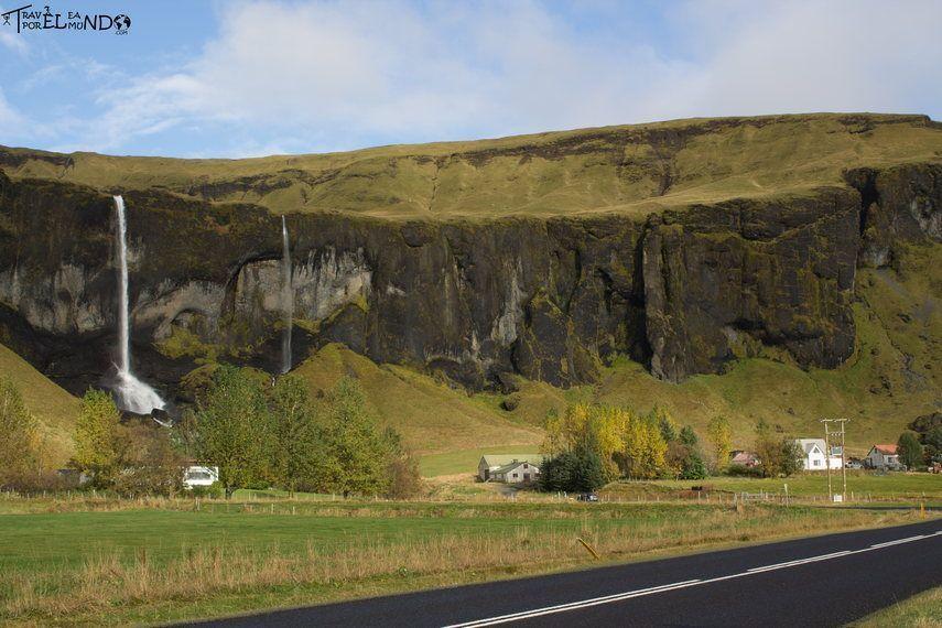 Montaña con cascadas a orilla de una carretera de asfalto