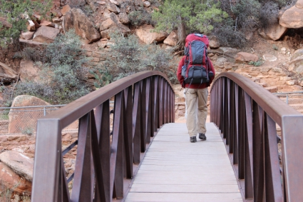 man_with_hiking_backpack_walking_across_bridge_596282