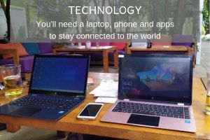 2 laptops, a phone and 2 beers on a table in an outdoor restaurant